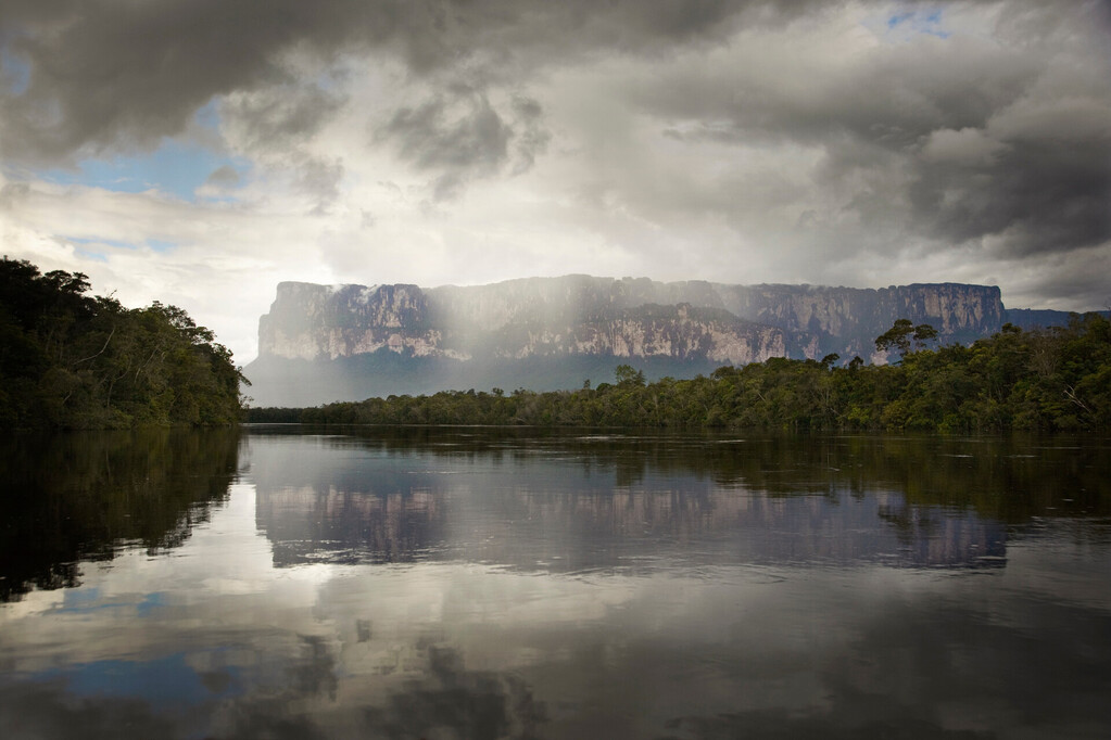 Tepuis, large flat topped mountains, stand all along the winding Canaima River, in Canaima National Park, Venezuela. Auyantepui seen here is home to Angel Falls